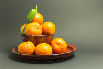 Still life studio shot of a red ceramic bowl and plate with black texture filled with fresh orange tangerines on gray background.