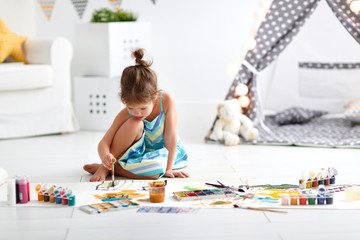 cute child girl paints at home
