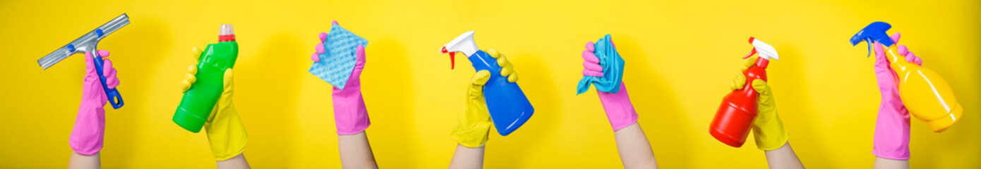 Cleaning concept - hands holding supplies on bright background Wall mural