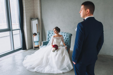A stylish bride and a beautiful bride are sitting on a sofa in a gray studio. The newlyweds look out the window.