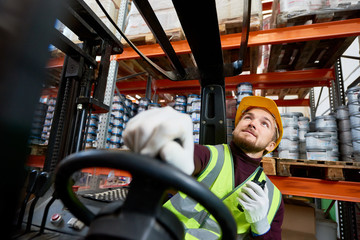 Low angle portrait of young warehouse worker sitting inside forklift moving goods from tall storage shelves and holding portable radio, copy space