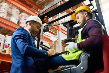 Side view portrait of mature businessman talking to warehouse worker sitting in forklift car
