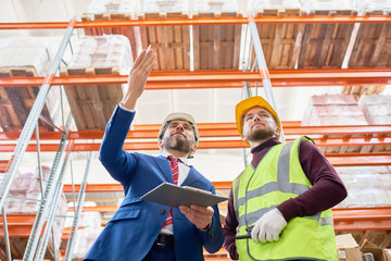 Low angle portrait of mature businessman holding clipboard talking to worker wearing hardhat and reflective jacket while discussing investment