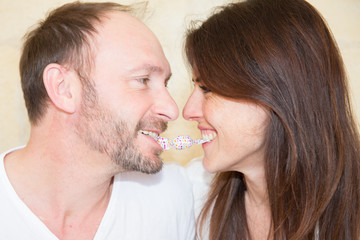 Young Couple sitting on the floor and looking at each other with candy between the teeth