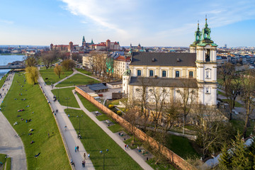 Staande foto Monument Krakow, Poland. Old city skyline, Paulinite monastery, Skalka church, far view of Wawel Cathedral and castle, Vistula River. People enjoying spring on the grass or walking. Aerial view, sunset light