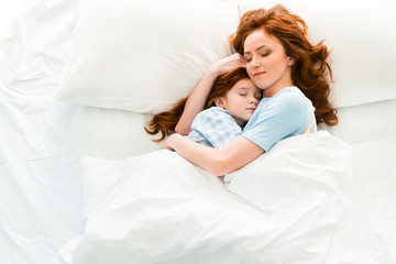 beautiful mother and daughter hugging and sleeping together in bed
