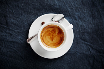 Cup of Coffee on dark blue cloth; seen from above