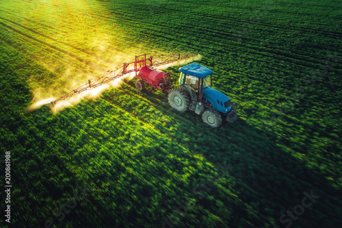 Wall mural Aerial view of farming tractor plowing and spraying on field