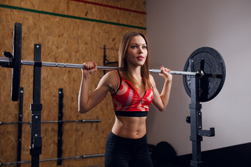 Photo of sporty woman with barbell in arms