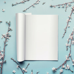 Mock-up of open magazine or catalog on pastel blue desktop background with twigs and white cherry blossom, top view, flat lay