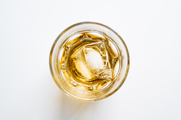 Glass of whiskey on ice from above on white background