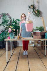 Full-length photo of florist with floral composition at table with flowers, boxes