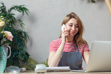 Image of florist woman talking on phone while sitting at table with computer