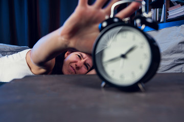 Portrait of dissatisfied woman with insomnia stretching arm to alarm clock at night