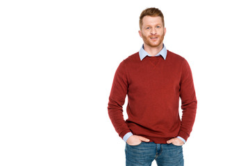 portrait of handsome redhead man standing with hands on pockets and smiling at camera isolated on white