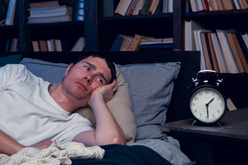 Photo of man with insomnia lying in bed next to alarm clock