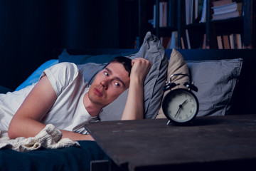 Picture of brunet with insomnia in bed with alarm clock