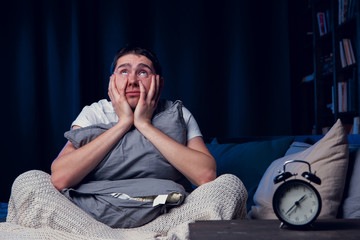 Picture of man with insomnia with pillow sitting next to alarm