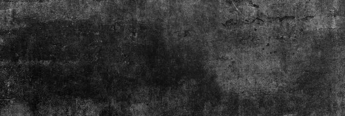 Textur einer fast schwarzen und alten Betonwand, auf die leichtes Licht fällt als Hintergrund