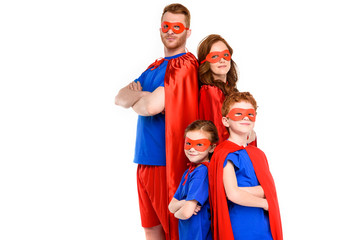 family in superhero costumes standing with crossed arms and looking at camera isolated on white