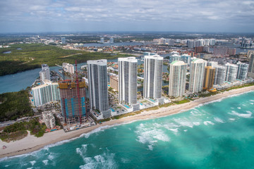 North Miami Beach buildings as seen from helicopter, Florida. Skyscrapers along the ocean, aerial view.