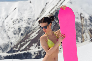 Young snowboarder woman in a swimsuit with a board on the background of mountain
