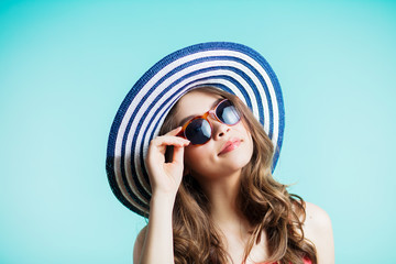 Young beautiful woman in bikini, hat and sunglasses standing on the beach. summer holidays and vacation concept.