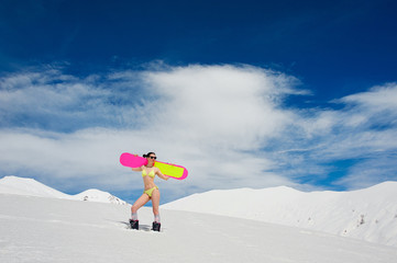 Slim sexy girl in a swimsuit with a snowboard on the shoulders
