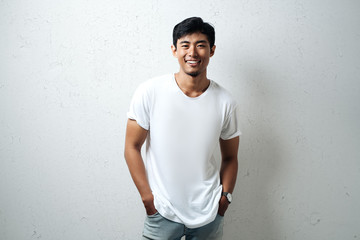 Smiling asian guy in white blank t-shirt, grunge wall, studio portrait