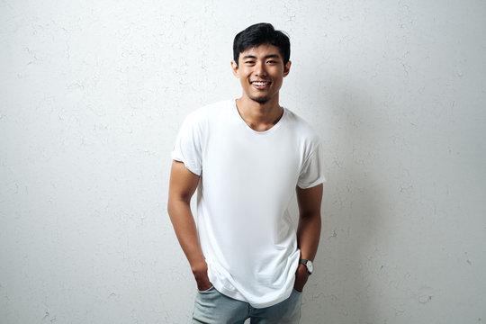 Smiling asian guy in white blank t-shirt, grunge wall, studio portrait