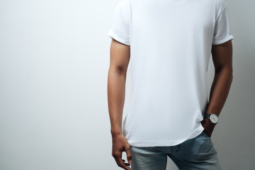 man in white blank t-shirt, empty wall, studio close-up, casual style