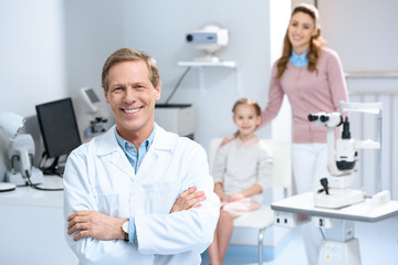 smiling ophthalmologist and mother with daughter in consulting room