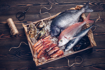 Fototapeten Fisch Fresh spanish fish and seafood in wooden box on wooden table