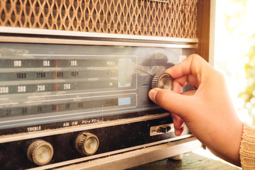 Retro lifestyle - Woman hand adjusting the button vintage radio receiver for listen music or news - vintage color tone effect.