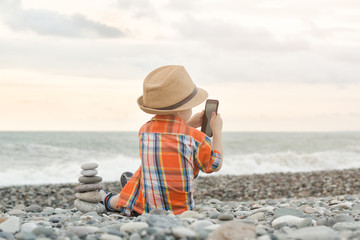 Little boy takes pictures on the smart phone. Sits on a pebble beach