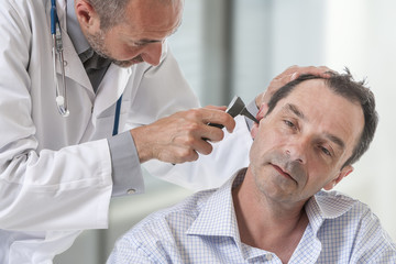 Mature man at medical examination, otoscopy