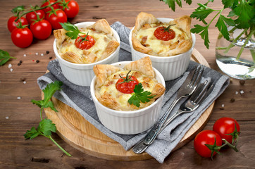 Ramekins with tasty chicken and bacon quiche on wooden board