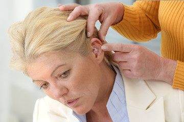Inserting your hearing instruments. The doctor assumes the woman hearing aid in your ear