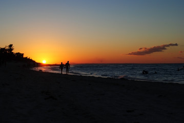 People are holding hands and walking on the beach during sunset. Sunset on the beach in Cuba. Orange sun on the horizon.