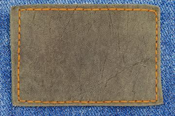 Black leather tag with an orange seam on denim blue jeans