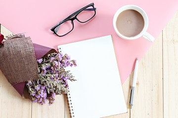 Business, planning, spring or summer concept : Top view or flat lay of open notebook paper, bouquet of dried wild flowers and coffee cup on desk table with copy space ready for adding or mock up
