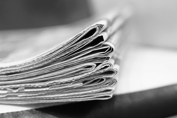 Fresh newspapers folded and stacked on the edge of table. Daily papers with business news at the office, morning at work. Pages with headlines, articles and photos, selective focus, blurred background