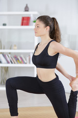 young lady exercising at home doing leg stretch