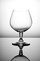 Empty glass for cognac on a gray background.