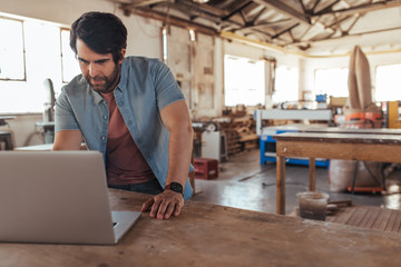 Craftsman working online with a laptop in his woodworking shop