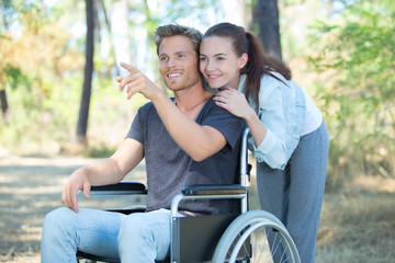 loving couple in wheelchair walking outdoors