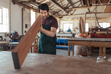 Young woodworker examining a plank of wood in his workshop