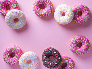 Pink and white donuts with celebration item on pink background