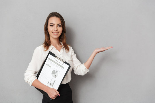 Amazing cheerful young business woman holding clipboard looking camera holding copyspace.
