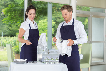 male female waiters setting tables at gourmet restaurant